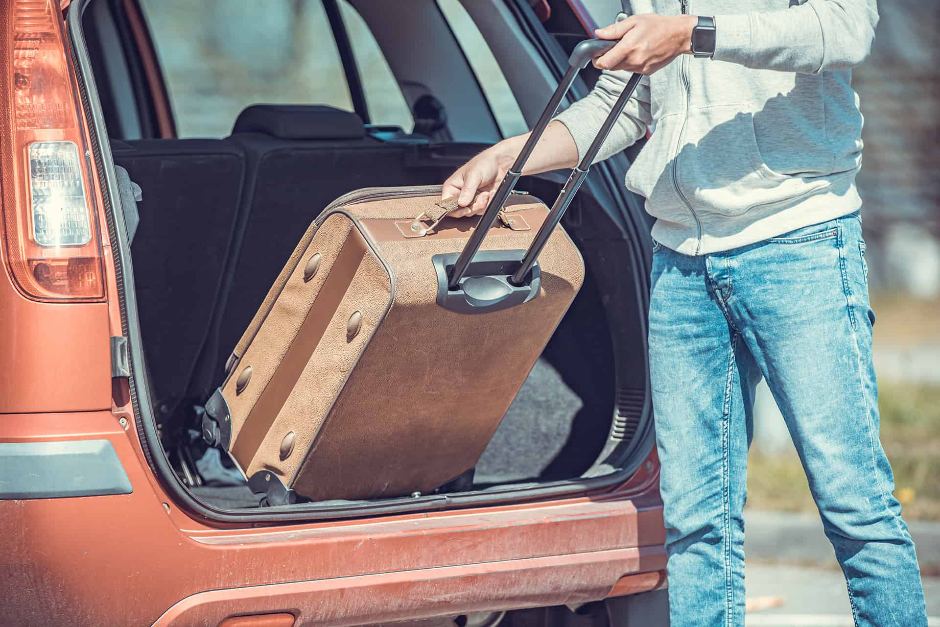 A young man puts luggage in the trunk of a car.